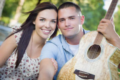 Beautiful Mixed Race Couple with Guitar in Park Stock Image