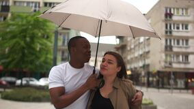 Beautiful mixed race couple running along a city street while it is raining. Black man holding an umbrella in his hands