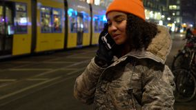 Beautiful mixed race female teenager girl young woman talking at night on cell phone at night with trams by Alexanderplatz Station. Beautiful mixed race female stock footage