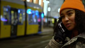 Beautiful mixed race female teenager girl young woman talking on cell phone at night with trams by Alexanderplatz Station, Berlin stock footage