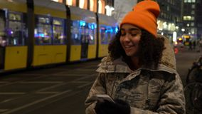 Young woman teenager using her cell phone at night with trams by Alexanderplatz Station, Berlin, Germany stock video footage