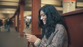 Beautiful mixed race girl with black hair in a Berlin subway waiting for a train and tapping a smartphone. Beautiful brunette mixed race girl in the Berlin stock video