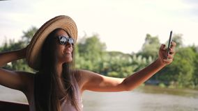 Beautiful Mixed Race Tourist Girl in Big Hat Taking Selfie Photo Using Mobile Phone and Cruise on Boat at River in. Thailand. 4K Slow Motion stock video footage