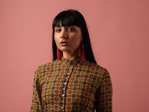 Mixed race woman with long black hair. Creative portrait of fashion model posing at studio on pink backbround. Beautiful mixed race woman with long black hair Royalty Free Stock Photography