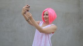 Beautiful mixed race woman in pink wig taking selfie using phone smiling and spinning enjoying life stock video footage