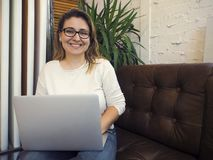 Beautiful mixed race woman sitting in a coffee shop using her laptop royalty free stock images