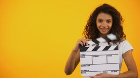 Beautiful mixed-race woman winking and holding clapper board, movie shooting. Stock footage stock video footage