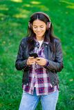 Beautiful mixed race young woman listening to music on headphones with smartphone. Hispanic hipster girl dancing to stock images
