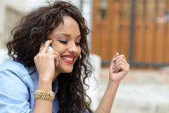 Beautiful mixed woman in urban background on the phone Royalty Free Stock Photo