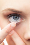 Beautiful model applying contact lens Stock Photo