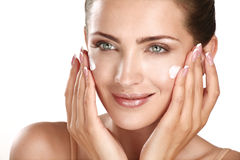 Beautiful model applying cosmetic cream treatmen on her face. On white royalty free stock photo