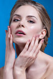 Beautiful model applying cosmetic cream treatment on her face on blue Stock Photo