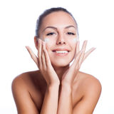 Beautiful model applying cosmetic cream treatment on her face on white Royalty Free Stock Photo