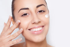 Beautiful model applying cosmetic cream treatment Stock Images