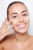 Beautiful model applying cosmetic cream Royalty Free Stock Photo