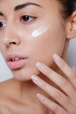 Beautiful model applying cosmetic cream treatment on her face white Stock Photography
