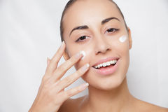 Beautiful model applying cosmetic cream treatment on her face white Royalty Free Stock Image