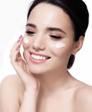 Beautiful model applying cosmetic cream treatment on her face on white fresh skin, smile Royalty Free Stock Photography