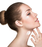 Beautiful model applying cream on face Royalty Free Stock Photography