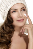 Beautiful model applying a creme on face protection from winter Royalty Free Stock Image