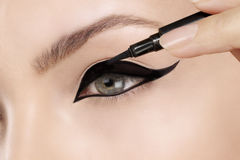 Beautiful model applying eyeliner closeup on eye Royalty Free Stock Image