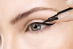 Beautiful model applying eyeliner closeup on eye Royalty Free Stock Images
