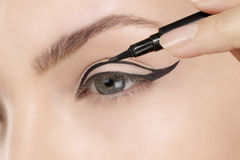 Beautiful model applying eyeliner closeup on eye Stock Image