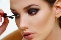 Beautiful model applying make up. Beautiful face model girl applying make up royalty free stock photos