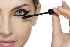 Beautiful model applying mascara on eyelashes  close up Stock Photography