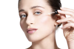 Beautiful model applying a skin serum treatment. On white Stock Photo