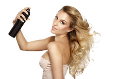 Beautiful model applying spray  on windy hair Royalty Free Stock Photos