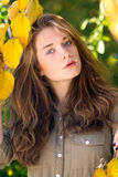Beautiful model with autumn leaves and fall yellow garden backgr Royalty Free Stock Photography