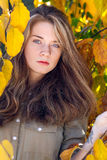 Beautiful model with autumn leaves and fall yellow garden backgr Royalty Free Stock Image