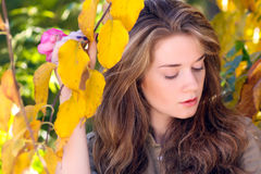 Beautiful model with autumn leaves and fall yellow garden backgr Stock Photo