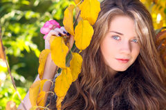 Beautiful model with autumn leaves and fall yellow garden backgr Stock Photography
