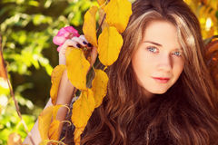 Beautiful model with autumn leaves and fall yellow garden backgr Stock Images