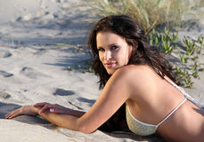 Beautiful model on the beach. Laying in the sand Royalty Free Stock Photo