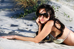 Beautiful model on the beach. Laying in the sand Royalty Free Stock Image