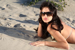 Beautiful model on the beach l. Aying in the sand Royalty Free Stock Images