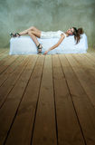 Beautiful model on bed, the concept of anger, depression, stress, fatigue. Beautiful model in white dress on bed, the concept of anger, depression, stress Stock Image