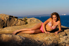 Beautiful model in a bikini lying on a rock. Royalty Free Stock Photography