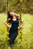 Beautiful model in black. Portrait of beautiful model in black on nature background, posing Royalty Free Stock Images