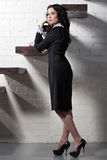 Beautiful model in black dress near stairway Stock Photography