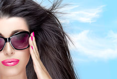 Beautiful Model in Black Fashion Sunglasses. Bright Makeup and M. Beautiful fashion model girl with healthy long hair in motion and stylish oversized black Stock Photos