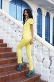 Beautiful model with black hair wearing elegant yellow suit Stock Image