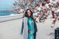 Beautiful model in blue dress and grey coat by spring blooming tree royalty free stock photography