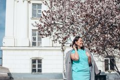 Beautiful model in blue dress and grey coat by spring blooming tree stock photos