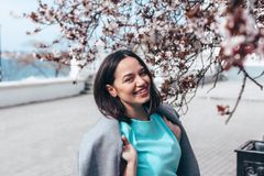 Beautiful model in blue dress and grey coat by spring blooming tree stock photo