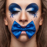 Beautiful model with blue make up and bow in mouth Royalty Free Stock Images