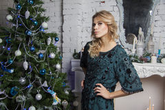 Beautiful model in blue silk dress near new year tree Royalty Free Stock Photography